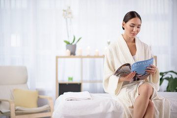 Dreaming about travel. Optimistic elegant young asian woman in white bathrobe is reading journal with smile while sitting on couch in comfortable spa center. Copy space in the left side