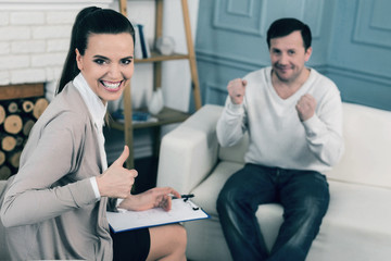 Feeling happiness. Attractive female keeping smile on her face and raising thumb while sitting in semi position