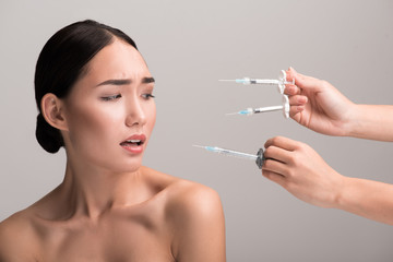 Gorgeous young naked asian woman is scaring of botox injections. She is looking with fear at syringes in hands of doctors near her face. Isolated background. Anti-aging skincare concept