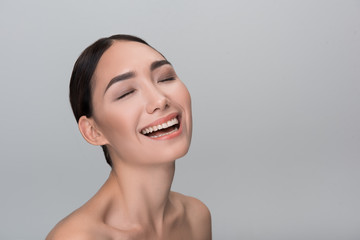 Delightful mood. Portrait of cheerful naked attractive young asian female is laughing with closed eyes. Isolated background and copy space in the right side. Progressive skincare concept