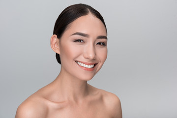 Great mood. Portrait of optimistic charming young naked asian girl is looking at camera with joy. Isolated background. Skincare and natural beauty concept