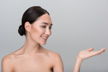 Best product. Happy pleasant young naked asian girl is holding hand palm up while looking at it with smile. Isolated background with copy space in the right side. Beauty and skincare concept