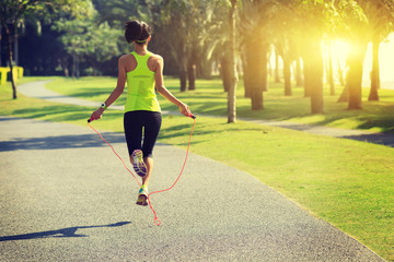 Young fitness woman jumping rope at tropical park