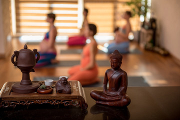 Women are kneeing on carpets. Close up of focus small figures of budda on table and clay brown cup
