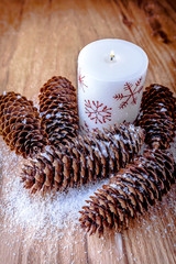 Christmas decoration, cones and decorative candle on wooden background.