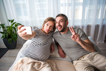 Portrait of carefree married couple making selfie while lying on bed. They are showing tongues to camera and laughing. Pregnant woman is holding smartphone
