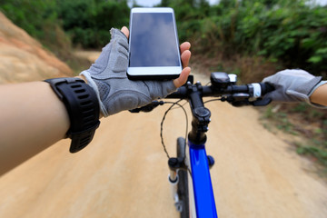 cyclist use smartphone for navigation cycling mountain bike on country road