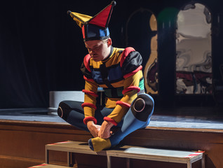 Actor dressed jester's costume in interior of old theater.