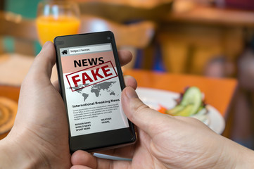 Man is holding smartphone and reading fake news on internet. Propaganda, disinformation and hoax concept.