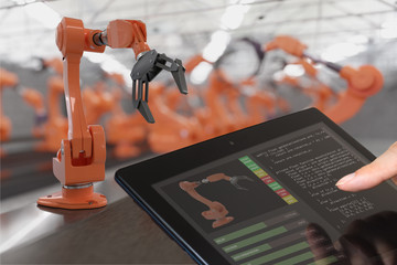 Programmer is controlling robotic arms with tablet. Automation and Industry 4.0 concept.