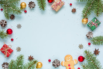 Christmas frame made of fir branches, red berries, gift boxes and pine cones on blue background
