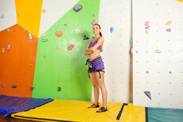 Sporty young woman in climbing gym