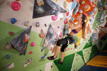 Young woman exercising in climbing gym