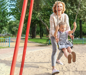 Cute little girl with grandmother in park on sunny day