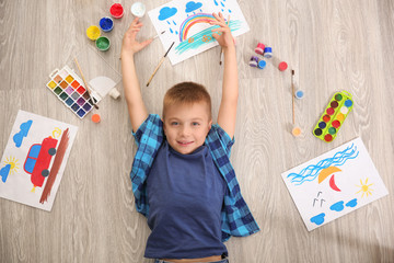 Cute boy lying among picture and painting materials on floor