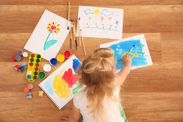 Cute girl painting picture on sheet of paper, indoors