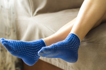 Woman feet in blue socks.Relaxing and comfort holiday concept.
