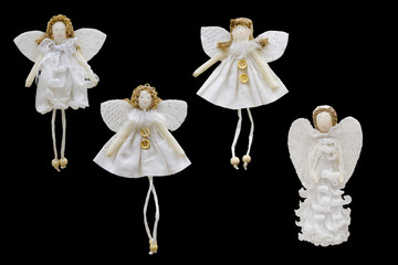 Christmas and New Year decorations for the Christmas tree: white figures of angels in the style of handmade. Isolated, black background.
