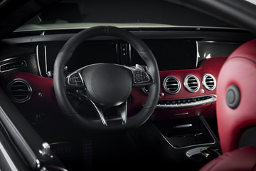 Luxury car inside. Interior of prestige modern car. Comfortable leather seats. Red perforated leather cockpit