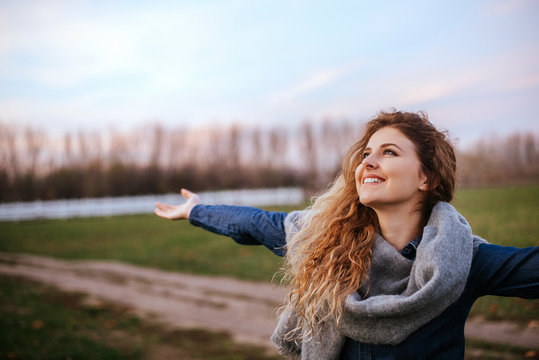 Side view portrait of delighted woman standing outdoors with her hands raised.