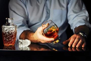 мужчина за барной стойкой пьет коньяк