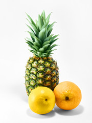 Isolated fruit photo Whole ripe pineapple and two oranges are lying on a white background Close-up fruit photo