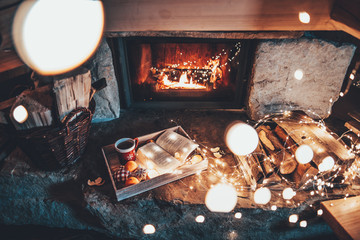 Warm cozy fireplace with real wood burning in it. Magical atmosphere. Cup of hot drink and book ready for evening relax. Cozy winter concept. Christmas and travel background with space for your text.