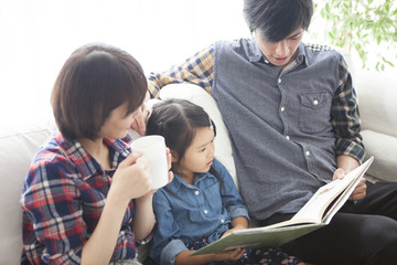 Dad and mommy are reading picture books for their daughter.