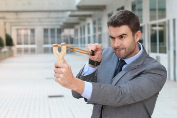 Competitive businessman using a slingshot