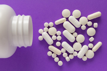 Group of assorted white tablets. Capsules spilling out of white bottle.