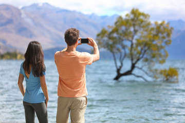 Wall Mural - New Zealand tourists taking phone pictures of Wanaka Lone Tree at lake. People looking at view of famous touristic attraction in south island, Otago Region, NZ.