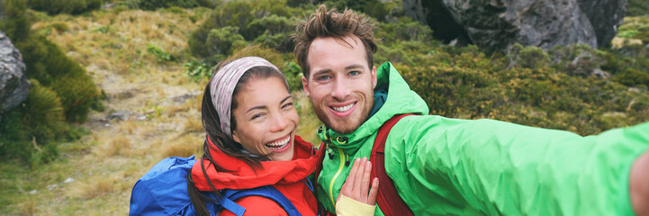 Travel selfie couple hikers taking smartphone picture on outdoor trail hike in outdoor nature. Active healthy happy people hiking panoramic banner. Multiracial young adults.