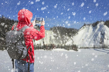 Young man taking pictures in winter snow field forest,Tourist in red jacket.