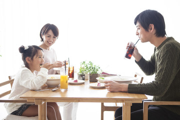 Dad, mommy and daughter are eating pasta.