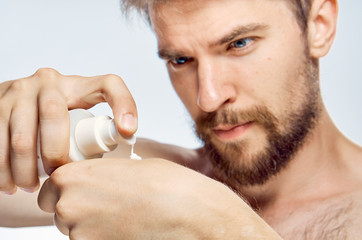 A man with a beard on a light background applies cosmetic cream on his hand