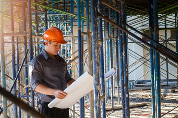 Engineer with blueprint in building construction site