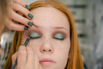 The girl makes up eyes in salon. Face care in salon.