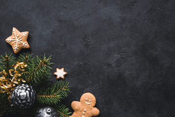Christmas background. Gingerbread cookies, fir tree, christmas toys and holiday decorations frame on blackboard or stone backdrop. Top view with copy space for text