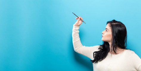 Young woman holding a pen on a solid background