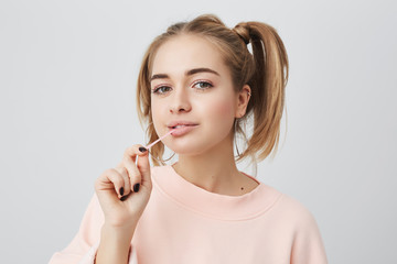 Picture of funny, playful, fashionable female student with appealing dark eyes, looking at camera, enjoying free time at home after lectures at university. Cute girl stretching chewing gum.