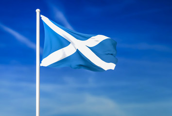 Waving flag of Scotland on the blue sky background