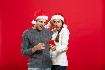 Christmas Concept - Young handsome and beautiful couple enjoy checking on mobile phone in christmas day.