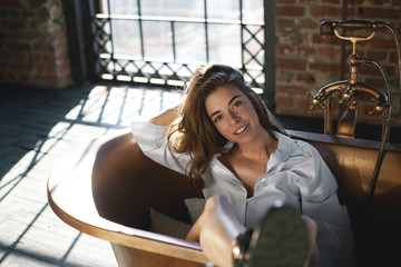 People, lifestyle, beauty, style and fashion concept. Picture of fashionable young lady wearing stylish shirt and shoes sitting in modern spacious bathroom, looking and smiling broadly at camera