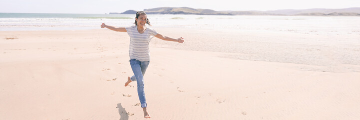 Wall Mural - Happy freedom woman running carefree having fun with open arms on beach vacation travel. Summer sunshine holiday destination girl. Life happiness panoramic banner.