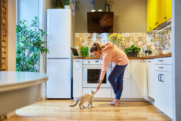 Happy woman stroking her charming cat while standing in her kitchen
