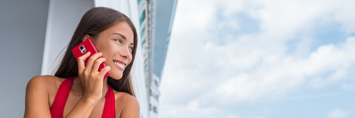 Wall Mural - Cruise ship woman calling on mobile phone during sailing holiday in the tropical Caribbean. Asian lady on international seas using smartphone for call at resort. Banner crop.