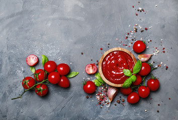 Fototapeta Tomato ketchup sauce with garlic, spices and herbs with cherry tomatoes in a wooden bowl on gray stone background, top view obraz