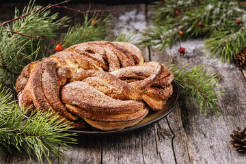 Cinnamon wreath bun and pine branches with snow cover on vintage wooden table. Christmas table decoration. Selective focus
