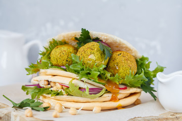 Fresh baked falafel in pita with vegetables, sprouts chickpeas and curry sauce