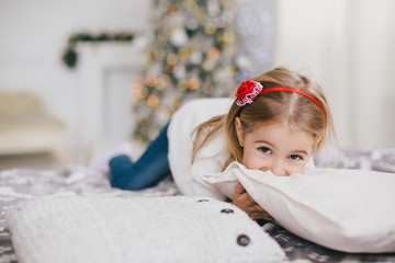 Happy little girl in a white sweater and blue jeans posing near christmas tree